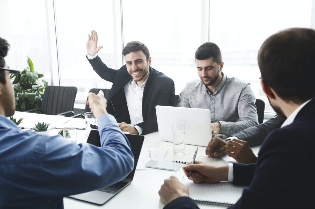 Businessman raising hand and asking question at meeting