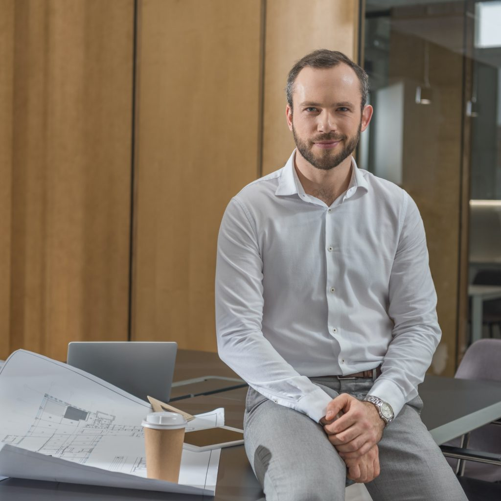 handsome architect sitting on table with plans at office