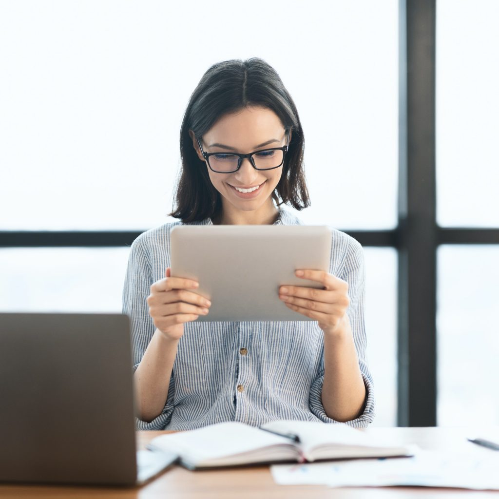 Young girl holding tablet and using laptop at office