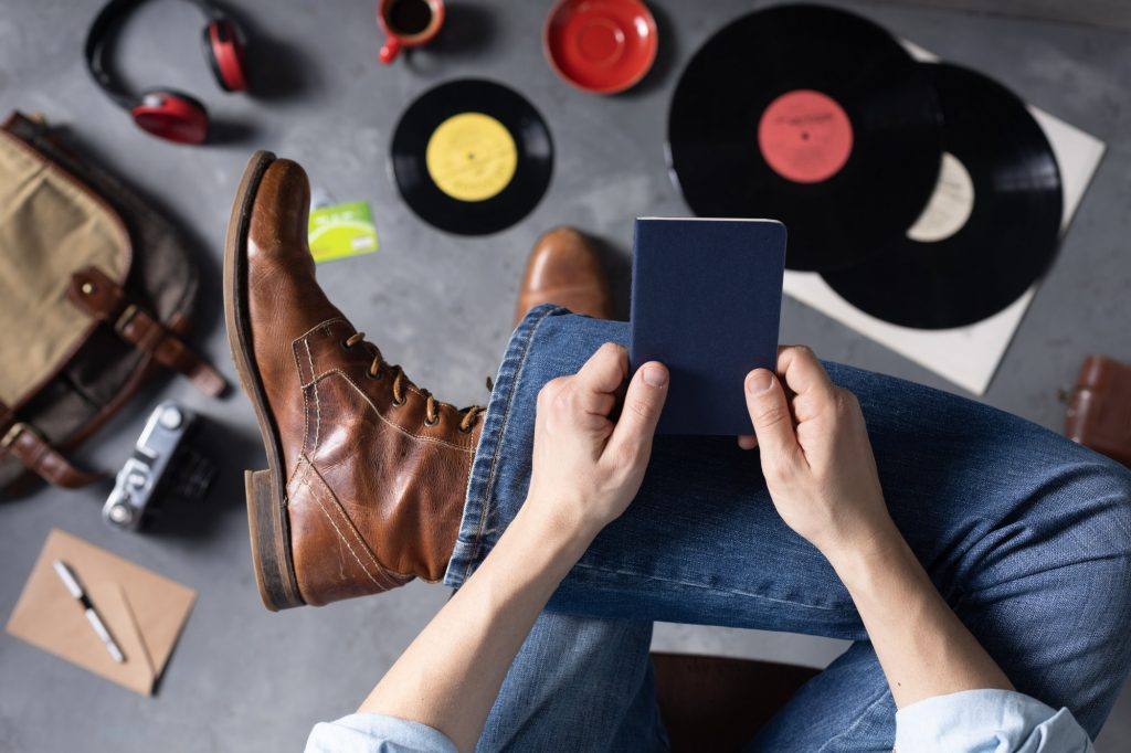 Men's hand holding passport or notebook and leg in jeans with old travel leather boots shoes